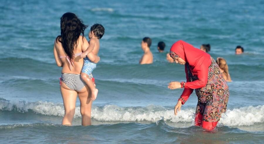 En tunesisk kvinde i burkini - og én i bikini - bader den 16. august på Ghar El Melh-stranden nær Bizerte nordøst for Tunis.