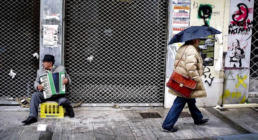 Athen: En mand spiller på harmonika foran en lukket butik for at tjene til dagen og vejen.