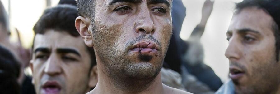 En iransk mand med teksten »bare frihed« skrevet på brystet, har syet sine læber sammen i protest, mens han venter på den græske side af den græsk-makedonske grænse.