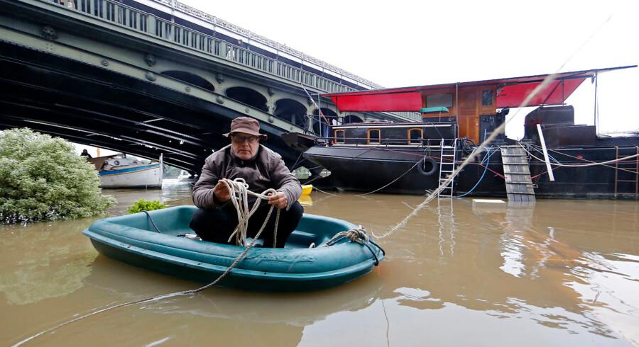 Massive oversvømmelser ved Seinen i Paris. En mand bruger gummibåd for at komme til sin husbåd, der normalt har direkte adgang til den landfaste jord.