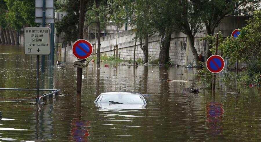 En efterladt bil er næsten helt dækket af vand i Paris.
