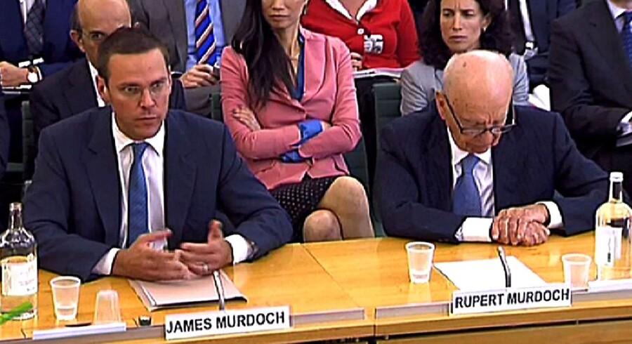 James Murdoch taler ved høringen i parlamentet, mens Rupert Murdoch hviler øjnene.