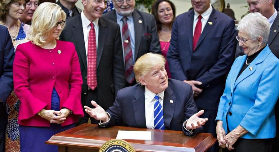 Præsident Donald Trump ved siden af Virginia Foxx, en republikaner fra North Carolina, og Liz Cheney, en republikaner fra Wyoming. Trump er ifærd med at at underskrive et præsidentielt dekret, der tilbageruller tidligere præsident Barrack Obamas påbud til de amerikanske stater, om at lade transpersoner benytte de toiletfaciliteter, der matcher det køn de identificerer sig med - og ikke nødvendigvis det køn de er født med.