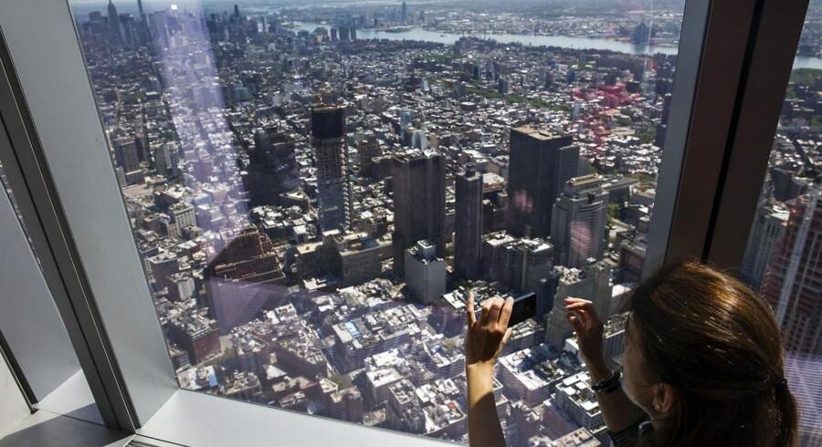 ARKIVFOTO. Det danske arkitektfirma Bjarke Ingels Group skal tegne et nyt World Trade Center ved Ground Zero i New York. Her kigger en kvinde ud fra det nyåbnede observatoriium i One World 29. maj.