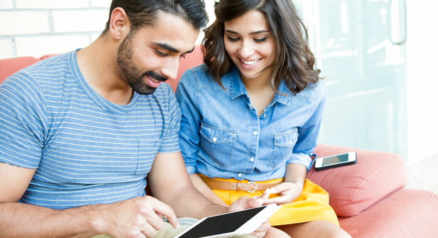Fashion couple sitting together and using a tablet