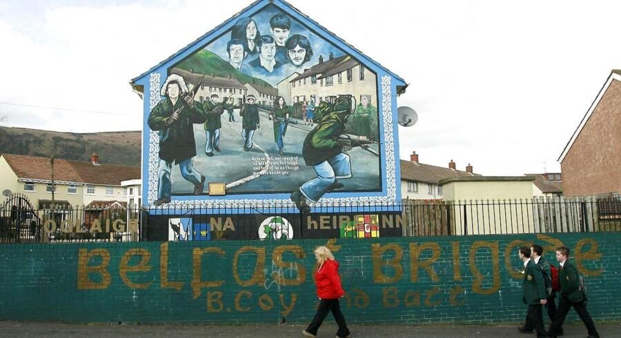 Beboere i Belfast passerer et af de gavlmalerier, som repræsenterer »The Troubles«, som konflikten kaldes lokalt. I næsten 30 år slog protestanter og katolikker hinanden ihjel, og det sluttede – stort set – med Langfredagsfredsaftalen 10. april 1998.