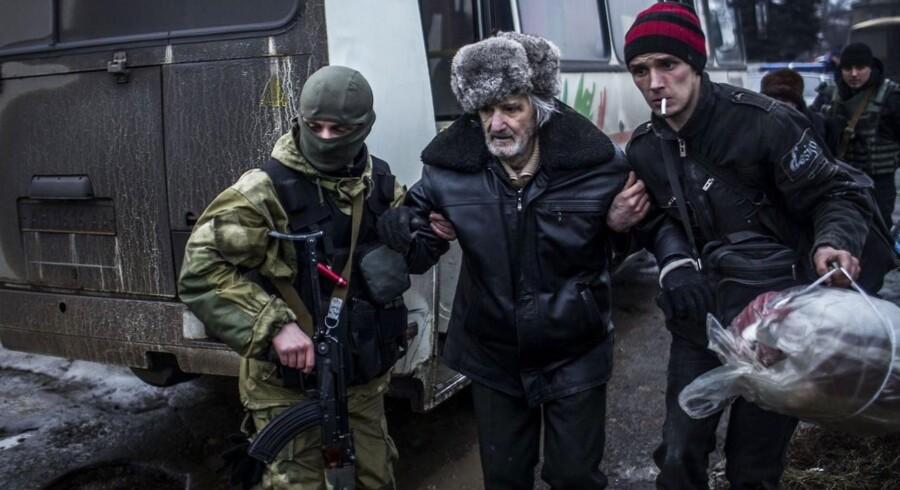En ældre mand bliver evakueret fra en forstad til den ukrainske by Donetsk.