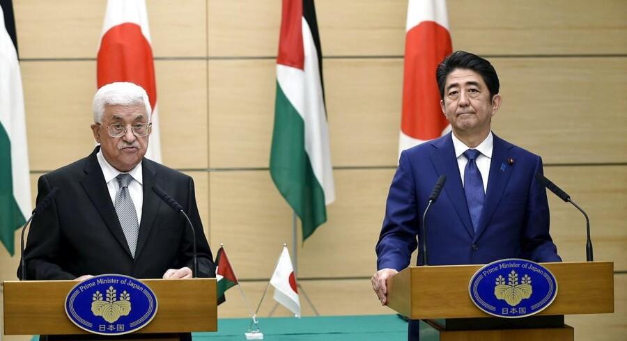 Den japanske premierminister Shinzo Abes (til højre) overvejelse om et lynvalg til parlamentet i Tokyo denne sommer er blevet langt mere kompliceret af den seneste tids finansielle uro.