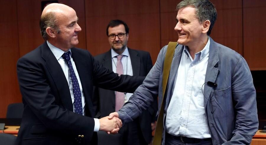 Spaniens Økonomiminister Cristobal Montoro Romero (tv) giver hånd til den græske finansminister Euclid Tsakalotos (th) ved mødet i EU.