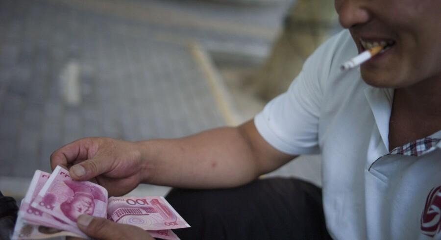 Borgere i Kina må officielt kun udføre det, der svarer til 50.000 dollar om året, men det er langt større beløb, der føres ud via ulovlige banker, som står bag diverse mere eller mindre udspekulerede fremgangsmåder. ?Arkivfoto: Fred Dufour/AFP
