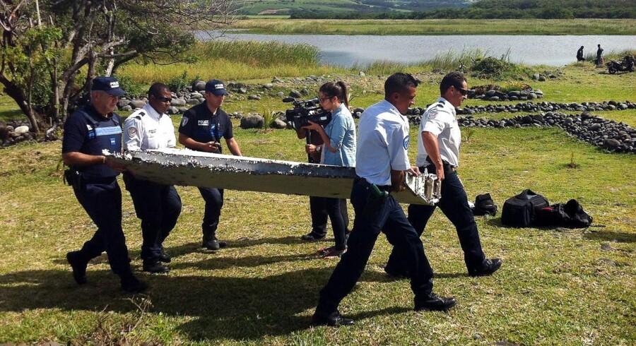 Politiet bærer en del af det, man formoder kan være rester fra MH370.