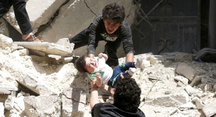 Syrere redder et lille barn ud af en ødelagt bygning efter et luftangreb i Aleppo 28. april.
