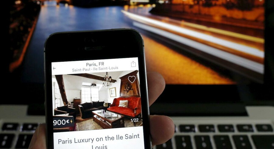 An illustration picture shows the Paris apartment offer by American actress Judith Freiha on the Airbnb web page displayed on a smatphone in front of a general view of the Ile Saint-Louis on the Seine river in Paris, France, August 9, 2015. Nowhere in the world has more accommodation available on Airbnb than Paris. Now the home-sharing website that has transformed budget travel to the French capital is giving its super-deluxe hotels a fright too. REUTERS/Christian Hartmann