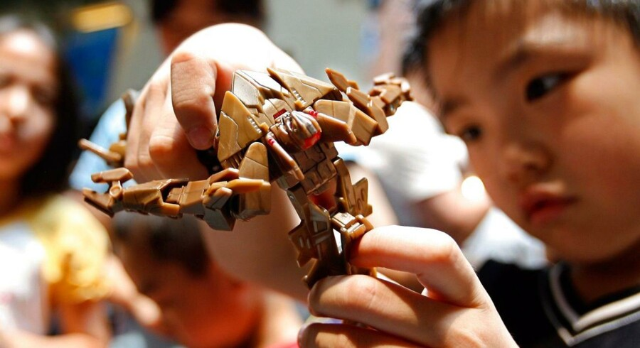 "(FILES)This July 22, 2007 file photo shows a young Chinese fan as he plays with a ""Transformers"" toy manufactured by Hasbro during a Transformers Expo in Beijing. AFP PHOTO/TEH ENG KOON"