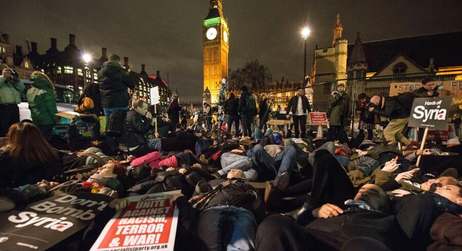 "Demonstrators lay on the road as they participate in a ""die-in"" during a protest outside the Houses of Parliament in central London on December 2, 2015, against the British government's proposed involvement in air strikes against the Islamic State (IS) group in Syria. Britain's parliament looks set to vote in favour of joining air strikes on Islamic State (IS) jihadists in Syria despite angry exchanges which have exposed deep divisions on military action. AFP PHOTO / CHRIS RATCLIFFE"