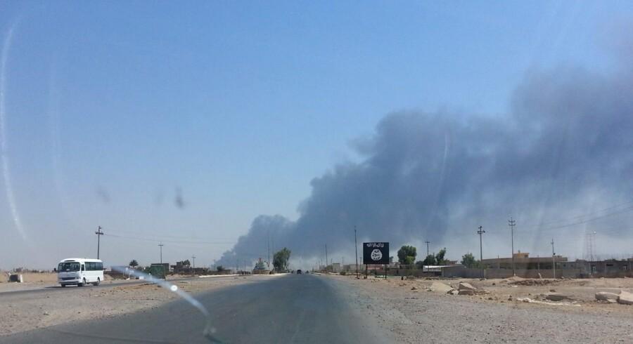 Røg rejser sig fra et olieraffinaderi i byen Baiji nord for Bagdad, hvor regeringsstyrker kæmper mod sunni-muslimske oprørere som støtter ISIS.