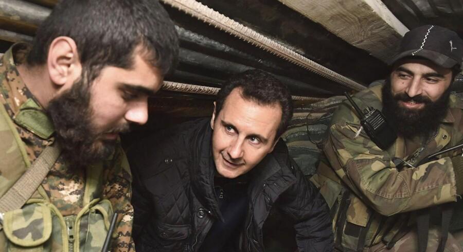 Den eneste løsning på borgerkrigen kan være, at Vesten forhandler med landet brutale diktator. Præsident Basher al-Assad ses på fotografiet, som kommer fra Syriens nationale nyhedsnureau SANA, besøge sine tropper i Damaskus' udkant.