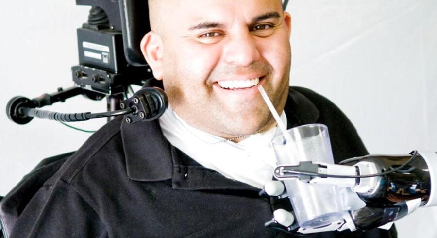 34-årige Erik Sorto tager en tår vand fra et glas, hans robotarm holder.