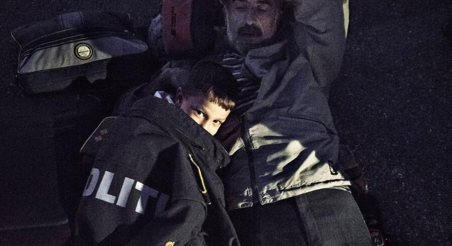 Med Sverige som destination på propfyldte tog blev omkring 600 flygtninge fra bl.a. Syrien stoppet mandag den 7. september 2015 i Rødby af det danske politi. Nogle gik med det samme ad motorvejen mod Sverige, mens andre blev i byen for at overveje beslutningen om at lade sig indskrive. Muhammad på 5 år og hans far Mahmud har været på flugt i 42 dage, siden de forlod Syrien. Selvom de meget hellere vil fortsætte mod Sverige, bliver de nødt til at vente på togperronen i Rødby for at få lidt hvile.De er ikke vant til Danmarks kølige sensommertemperatur, så derfor har en politimand lånt Muhammad sin jakke som dyne.