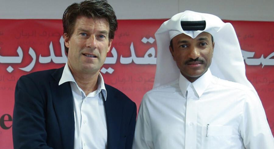 Cheftræner for klubben Lekhwiya, Michael Laurup, poserer med Lekhwiyas vicepræsident, Khalifa Khamis. I begyndelsen af juli 2014 efter at Laudrup har skrevet under på en et-årig kontrakt med klubben fra Qatar.