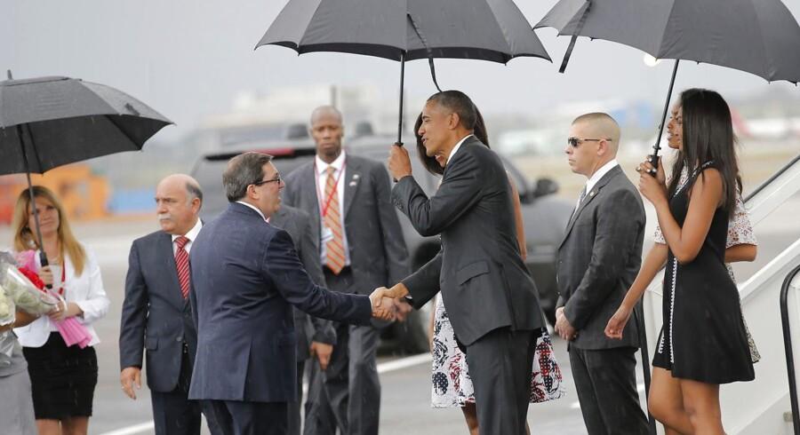 Den amerikanske præsident Barack Obama giver hånd til Cubas udenrigsminister, Bruno Rodriguez, efter Obama med familie er landet i lufthavenen i hovedstaden, Havana