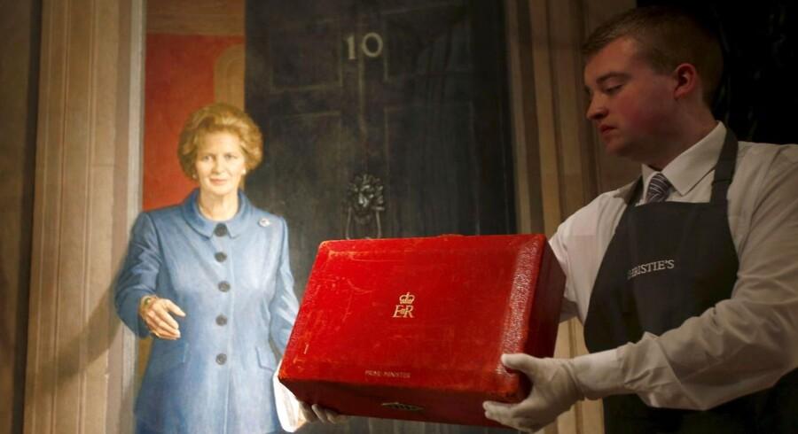 En ansat holder en af genstandene ved Margaret Thatcher-auktionen op.