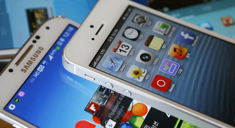 Apple og Samsung slås om ligheder i design og funktioner på deres topprodukter. Her ses Apples iPhone 5 (øverst) og Samsungs Galaxy S4 (underst), som for nylig har fået en storebror, Galaxy S5. Foto: Kim Hong-Ji, Reuters/Scanpix
