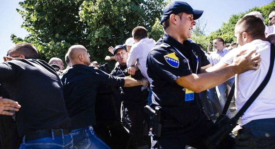 Politifolk og bodyguards beskytter premierminister Aleksandar Vucic fra de vrede masser.
