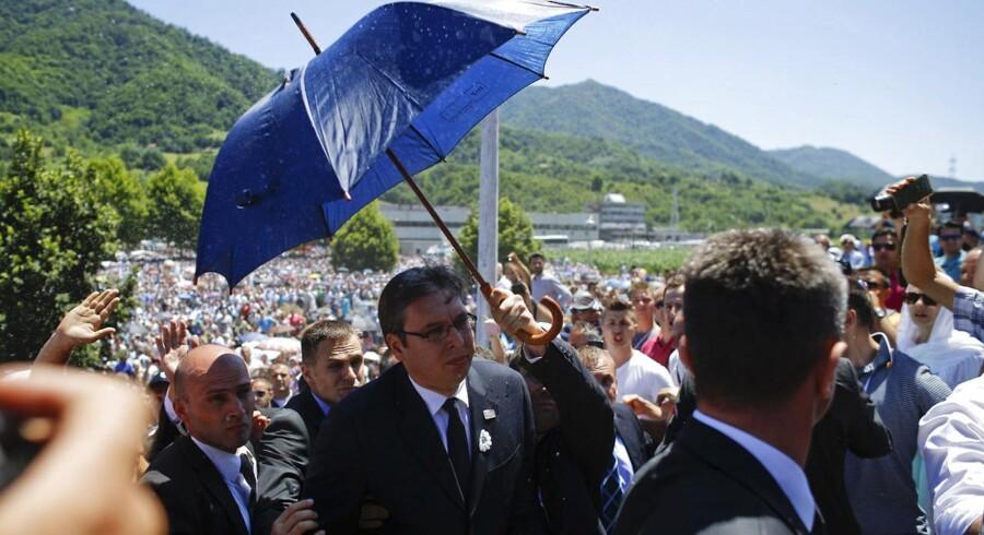 Bodyguards beskytter premierminister Aleksandar Vucic mod sten- og flaskekast med en paraply.