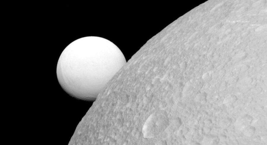 Saturns beskedne ismåne Enceladus gemmer sig bag en anden saturnmåne, Dione. Nu viser forskning, at Enceladus i sit dybe hav under isen rummer komplekse organiske molekyler, der er nødvendige for liv, som vi kender det.