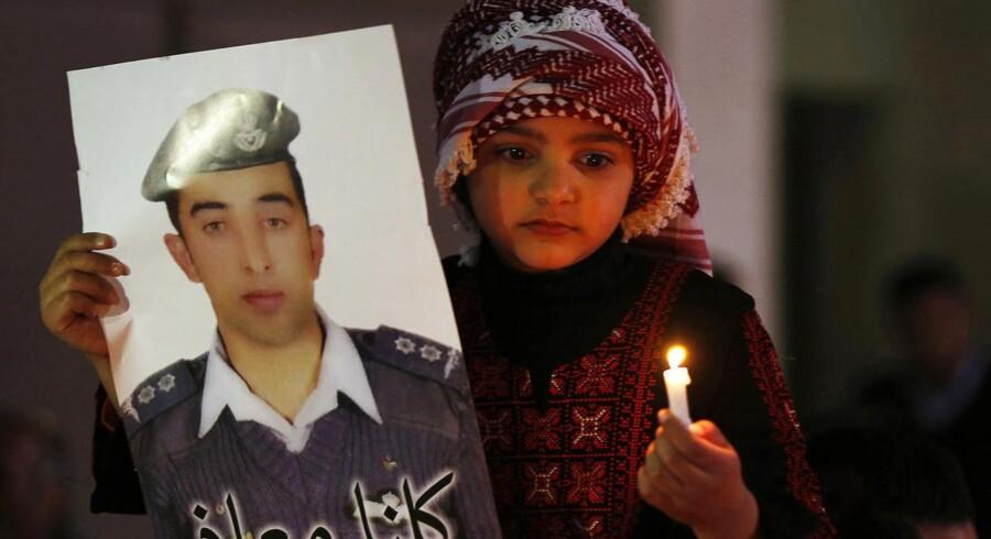 En jordansk pige holder et billede af piloten Muath al-Kasaesbeh, der blev fanget og brændt levende af Islamisk Stat.