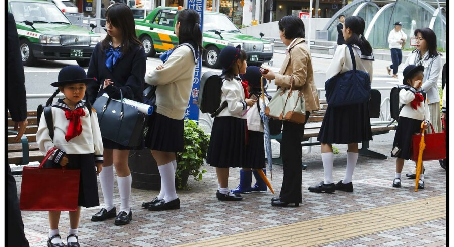 Japanske skolepiger i skoleuniform med deres forældre ved skolebus.