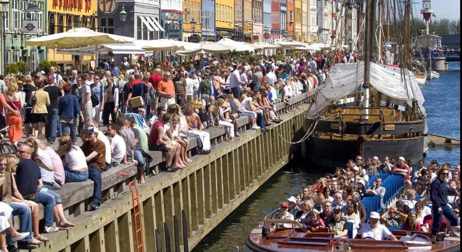 Københavnere og turister, som ikke lader sig afskrække af prisniveauet, myldrer i Nyhavn på en sommerdag.