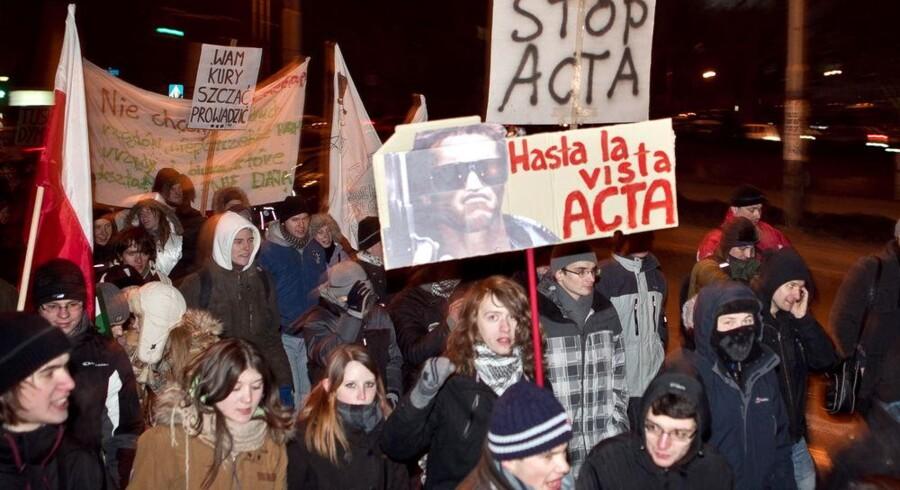 """""""Stop ACTA"""" og """"Hasta la vista, ACTA"""" stod der på demonstranternes skilte, da de i fredags gik i gaderne i bl.a. den polske by Wroclaw. Foto: Maciej Kulczynski, EPA/Scanpix"""