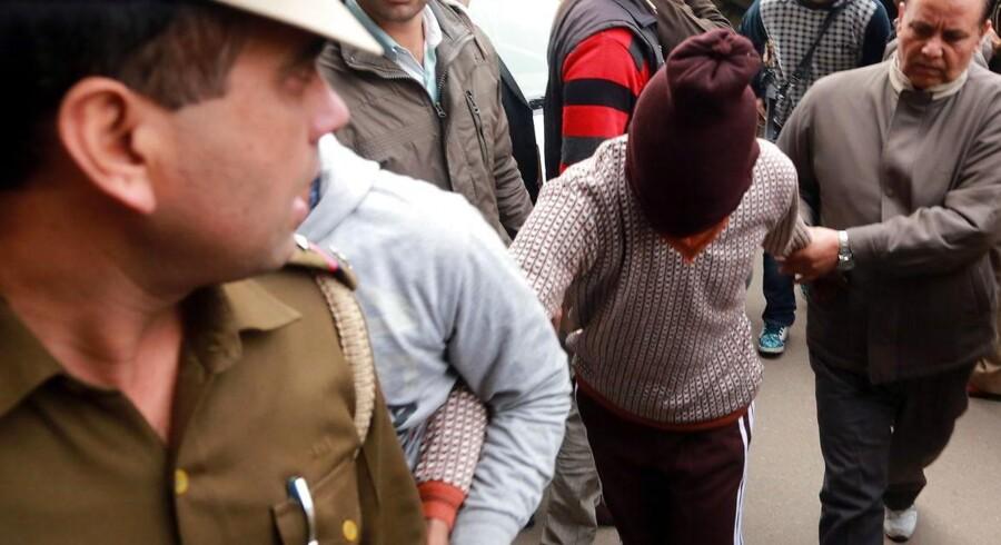 Indisk politi eskorterer en af de sigtede i sagen om voldtægten på en dansk turist i New Delhi.