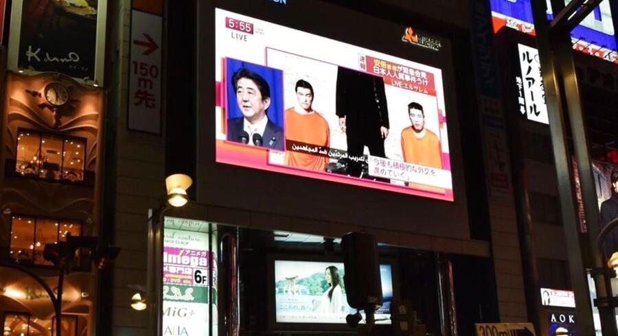 En storskærm i Tokyo sender en nyhedsrapport om kidnapningen af jo japanere. Premierminister Shinzo Abe kræver dem løsladt øjeblikkeligt.