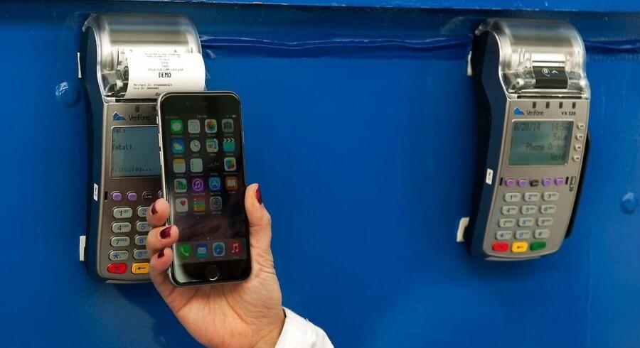 Mobilbetalingstjenesten Apple Pay virker kun på de nye iPhone 6-telefoner men er designet, så man holder sin telefon hen til en kortlæser, hvorpå pengene for købet trækkes på et af de kreditkort, som er lagt ind i Apples software. Men flere store kæder vil ikke være med. Foto: Bryan Thomas, Getty/AFP/Scanpix