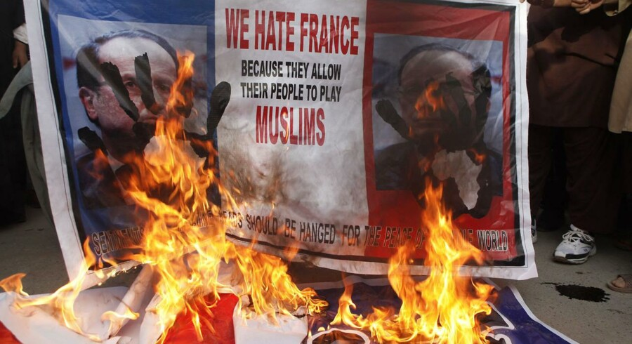 Bannere med det franske flag og præsident Francois Hollandes ansigt portrætteret brændes af i Pakistan som protest mod Charlie Hebdos karrikaturer af profeten Muhammed.