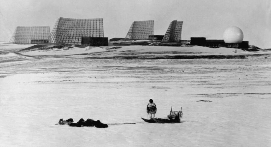 En grønlænder ved sin hundeslæde kigger mod ?Thule-basen i 1966. Foto: Scanpix