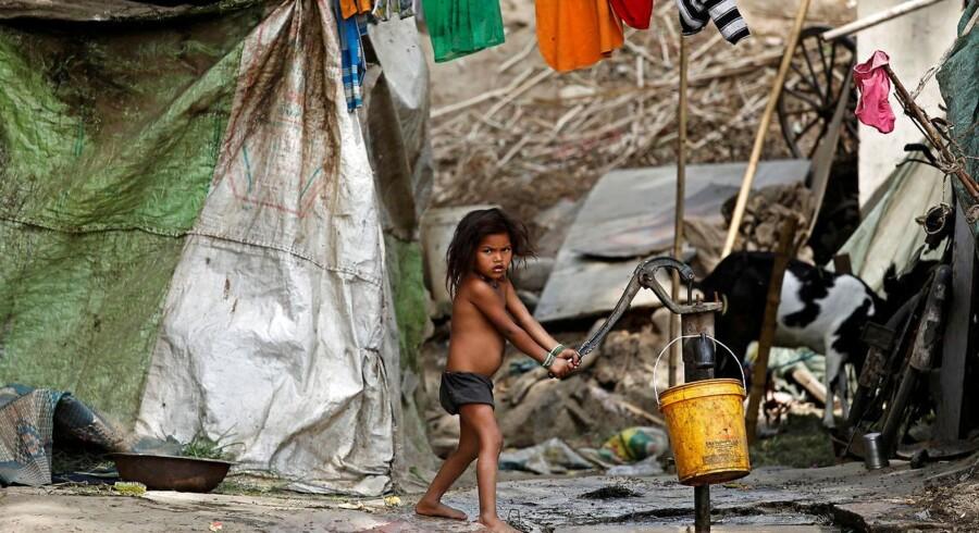 En pige pumper vand i en forstad til New Delhi. Overalt i Indien er det blevet sværere at finde vand nok. Foto: Saumya Khandelwal/Reuters/Scanpix