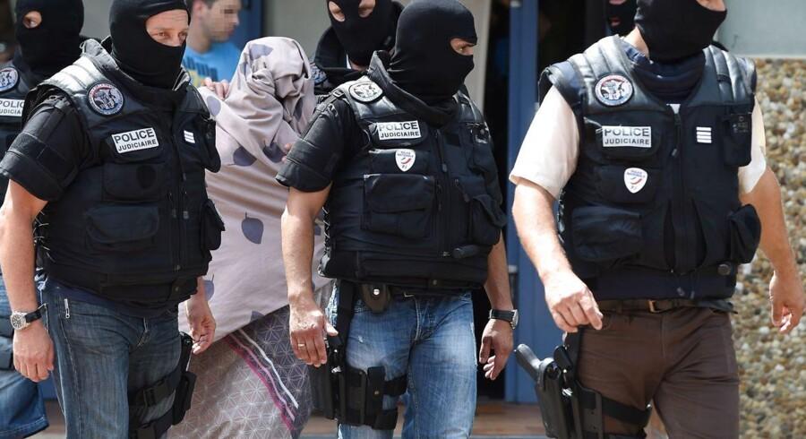 Franske specialstyrker eskorterer en uidentificeret kvinde ud efter en aktion i kølvandet på terrorangrebet i Lyon.
