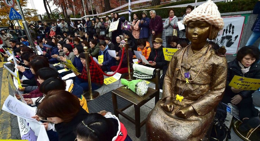 Demonstranter sidder ved siden af statuen af en sydkoreansk teenagepige, som er rejst som minde for de sydkoreanske piger, der blev brugt som sexslaver af japanske soldater under Anden Verdenskrig.