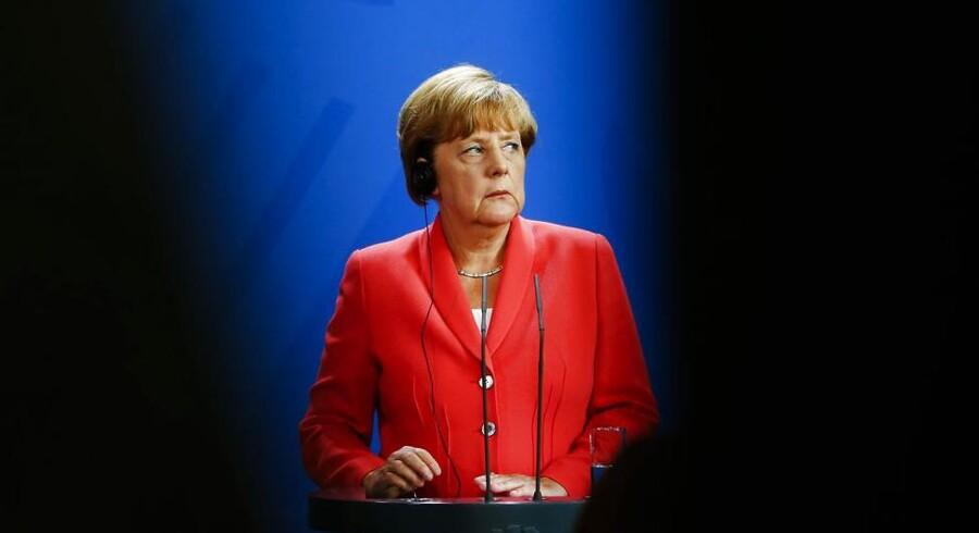 Kansler Merkel lytter til oversættelsen af de franske og ukrainske præsidenter Francois Hollandes og Petro Poroshenko, som hun mødtes med i Berlin.