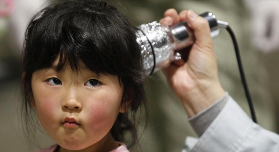 En pige bliver testet for mulig radioaktiv stråling på et evakueringscenter efter atomulykken i Fukushima. Nu skal 300.000 børn, der bor i nærheden af det tidligere kraftværk testes for misdannelser på skjoldbruskkirtlerne.
