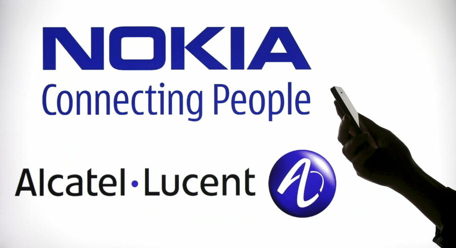 "A woman holds a smartphone in front of a screen displaying both Nokia and Alcatel-Lucent logos in this file photo illustration shot in Paris, France, April 14, 2015. Alcatel-Lucent is expected to hold its AGM this week. REUTERS/Benoit Tessier/Files GLOBAL BUSINESS WEEK AHEAD PACKAGE - SEARCH ""BUSINESS WEEK AHEAD MAY 25"" FOR ALL IMAGES"
