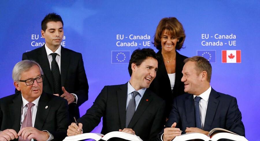 Canadas prmierminister Justin Trudeau (i midten) underskrev søndag frihandelsaftalen mellem Canada og EU i Bruxelles. EUs rådsformand Donald Tusk (th) og EU-kommissionsformand Jean-Claude Juncker (tv) underskrev på vegne af EU. REUTERS/Francois Lenoir