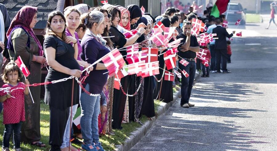 Asylsøgere på Langeland venter med dannebrogsflag på besøg af dronning Margrethe. Foto fra sidste sommer.