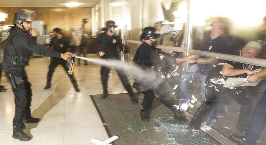Politifolk forsøger at storme glasdørene, men bliver mødt med tåregas af Kongressens eget politi. EPA/Joédson Alves