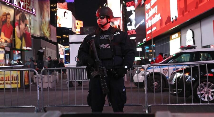 En politimand står på vagt ved Times Square i New York nær den metrostation, hvor en mand detonerede en bombe mandag 11. december 2017.