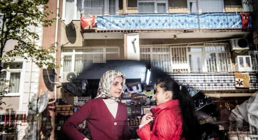 Rukiye (tv.) var 10-12 år gammel, da Tyrkiets præsident, Recep Tayyip Erdogan, boede i ejendommen overfor hendes families kiosk. Erdogans gamle hjem er synligt via genspejlingen i butiksvinduet. Rukiye husker stadig, at Erdogan hver fredag kom ned i hendes fars kiosk og købte slik til børnene på gaden. »Han var venlig og havde et stort hjerte,« siger hun.